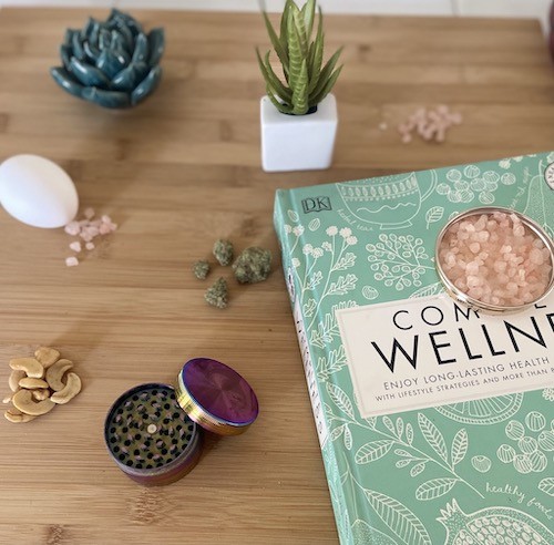 Cannabis and Food. Wooden cutting board with egg in shell, pile of cashews, cannabis buds, cannabis grinder, pink Himalayan sea salt, ceramic succulent, succulent in vase, and teal wellness book.