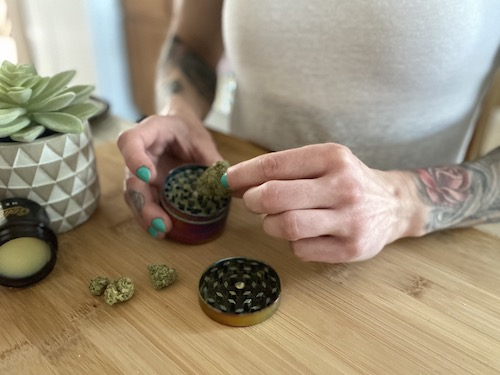 Image of Sam Coogan's hands placing cannabis buds into cannabis grinder over wooden cutting board with CBD balm and potted succulent.