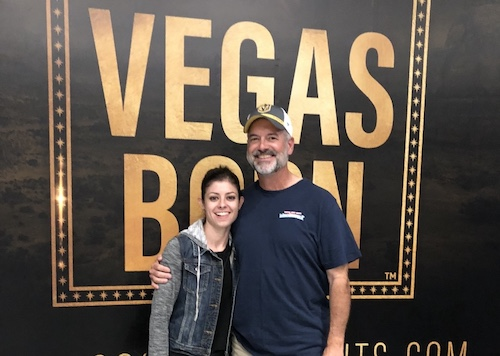 """Image of Sam Coogan and her dad standing side by side in front of a """"Vegas Born"""" sign inside Vegas Golden Knights' City National Arena."""