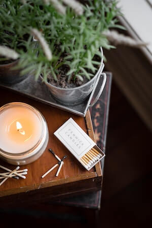 """cannabis 101 - candle burning with matches and a potted plant on an end table from Photo by <a href=""""https://unsplash.com/@bannon15?utm_source=unsplash&utm_medium=referral&utm_content=creditCopyText"""">Bannon Morrissy</a> on <a href=""""https://unsplash.com/s/photos/aroma?utm_source=unsplash&utm_medium=referral&utm_content=creditCopyText"""">Unsplash</a>"""