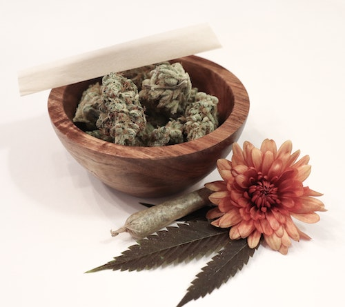 cannabis 101 understanding terpenes - cannabis buds in wooden bowl with pink flower and joint from Photo by Botanical Rising on Unsplash