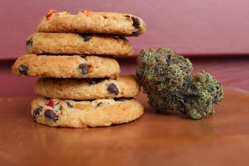 stack of 5 chocolate chip cookies next to a cannabis bud on a wooden table