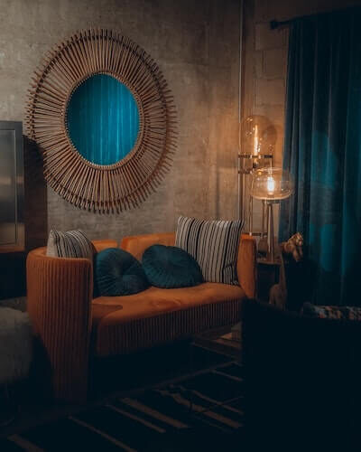 dimly lit room with circular rattan mirror hanging on wall with orangey couch, two teal round throw pillows, a floor lamp and teal curtains