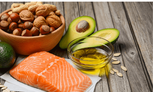 the endocannabinoid diet an Endocannabinoid System Booster - Image of bowl of walnuts, peanuts, and hazelnuts next to a sliced avocado with pit in one side, small glass bowl of oil, seven pumpkin seeds, and one slice of raw salmon on a wooden background