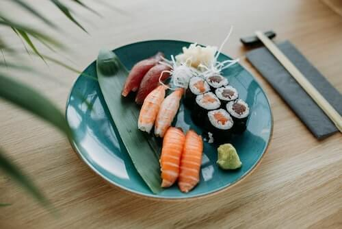 the endocannabinoid diet an Endocannabinoid System Booster sushi image of salmon nigiri, shrimp, nigiri, tuna nigiri, salmon roll, tuna roll, ginger and wasabi and round, teal plate with chop sticks on bamboo table