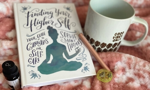 image of book titled finding your higher self by Sophie Saint Thomas, eucalyptus essential oil, CBD vape pen, cannabis buds, grinder and coffee mug that says good vibes only on light pink blanket