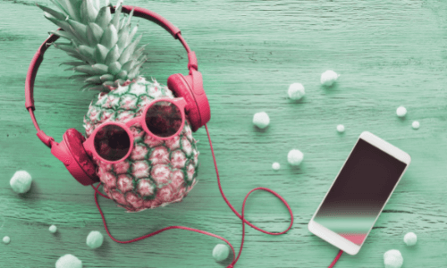 facts about pineapple - pineapple in pink sunglasses wearing pink headphones with a smart phone on a mint green background