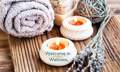 welcome in wellness with to improve mental health with a rolled up towel, two bars of soup, two tea light candles and herbs on a wooden background